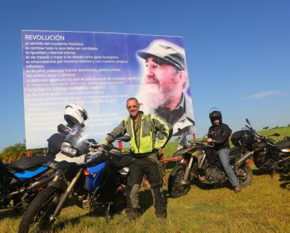 Motorcycle - Christopher P Baker and Cuba Motorcycle Tours members beside a billboard of Fidel Castro, Cuba;